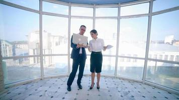 hombres de negocios, hombre y mujer, discuten el proyecto de trabajo en un edificio de oficinas moderno cerca de una ventana panorámica limpia. concepto de negocio. disparar steadicam video
