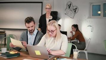 mujer gerente viene a la mesa y dando instrucciones. reunión del equipo de negocios creativos en la oficina de inicio moderna
