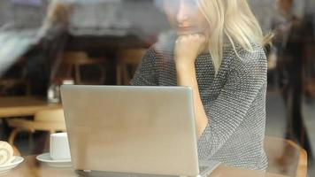 bella giovane donna d'affari seduto in un caffè con un computer portatile