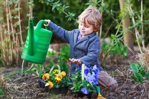 Niñito jardinería y plantar flores en el jardín