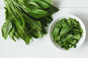 Fresh sorrel plant leafs in white bowl on rustic background photo