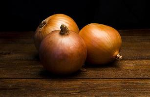 Three onions on a wooden table photo