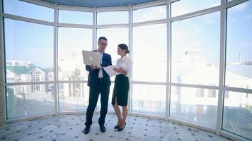 Businessmen man and woman discuss work project in a modern office building near clean panoramic window. Business concept. Steadicam shoot