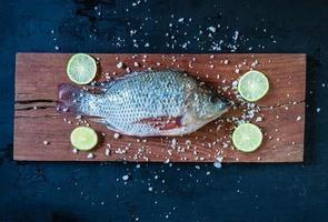 pesce tilapia fresco su tavola di legno