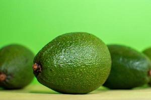 Avocados with green background