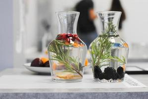 Vases with rosemary and fruit