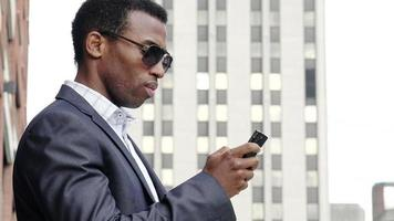 young handsome businessman using cell phone or smartphone in the city