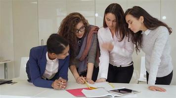 Cuatro mujeres se paran cerca de la mesa con papeles y tabletas.