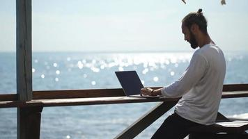 Young professional businessman using modern laptop outdoors