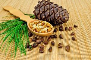 noten en kegel van ceder op een bamboemat
