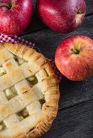 Apple pie and fresh apples on table