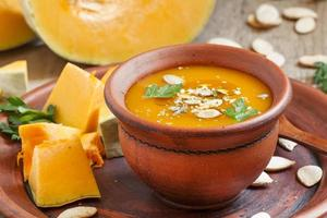 Pumpkin soup with oil and seeds in a clay bowl