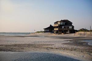 A beach house on the beach of an ocean photo