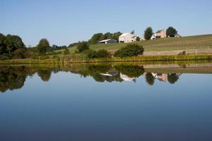 White farmhouse reflects in pond