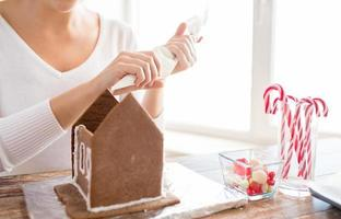 close up of woman making gingerbread houses photo