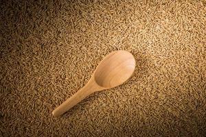 Cucharones de madera sobre fondo de arroz con cáscara