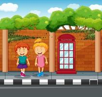 Happy girls next to a pay phone outdoors vector