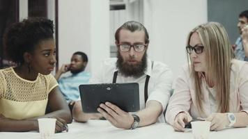 deux femmes et un homme discutant et utilisant une tablette