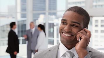 hübscher Geschäftsmann auf einem Handy in einer Bürolobby