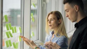 dois funcionários de escritório colam adesivos coloridos na janela
