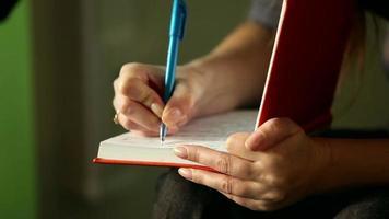 niña escribe una pluma en el cuaderno