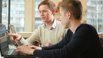jovem que trabalha no escritório dos laptops do projeto. eles conferem sobre um assunto importante e é mostrado no monitor. o conceito de trabalho em equipe video