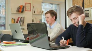 jovem que trabalha no escritório dos laptops do projeto. um está ligando para o cliente e registra as respostas. o conceito de trabalho em equipe