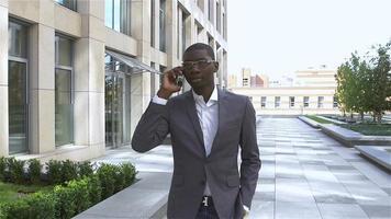 empresario afroamericano trabajando: hablando por teléfono celular. mirada estilizada de la foto, cámara lenta video