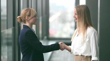 Two businesswoman shaking hands video