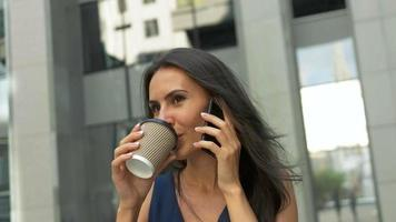 Attractive business woman walking in the city, drinking coffee and talking on a phone in the morning video