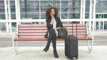 wunderschöne junge lächelnde afroamerikanische Geschäftsfrau, die auf der Bank am Flughafen sitzt und auf Handy spricht. städtischer Glaswandhintergrund