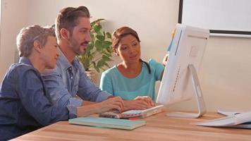 Equipo de negocios creativos usando la computadora y mirando a la cámara video