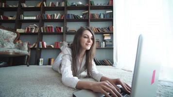 mulher jovem e bonita feliz usando laptop, dentro de casa