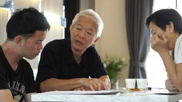 padre e figlio asiatici discutono di investimenti immobiliari. acquisto casa o condominio. parlando di finanza, profitto e rendimento