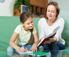 mãe com filha fazendo lição de casa