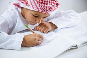 Arabic little boy doing homework photo