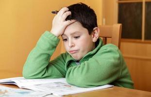 niño aburrido y cansado haciendo la tarea