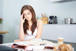 Young student woman with lots of books studying
