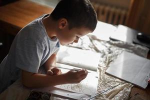 Little boy painting coloring book at home