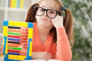Infeliz chica pelirroja aburrida haciendo sus deberes en casa