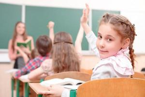 Pupil raising hand turned away from teacher