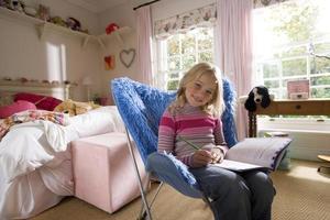Chica en el dormitorio haciendo los deberes en la silla de pila de pelusa azul