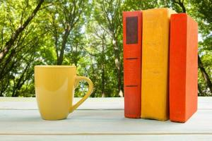 Stack of colorful books and cup on wooden table