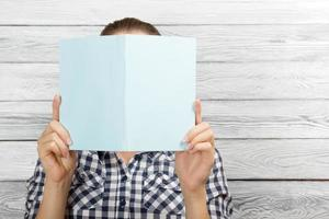 Woman reading a book and covering her face photo