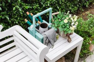 Gardening tools on white wooden table and bench