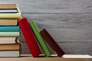Stack of colorful books on wooden table. Back to school.
