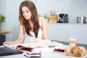 Young student woman with lots of books studying photo