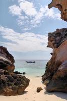 rocas en la playa, barco en el mar más allá foto