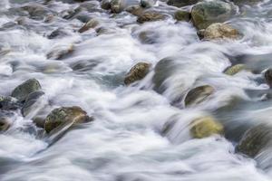 agua blanca y sedosa que fluye río abajo sobre las rocas y cantos rodados foto