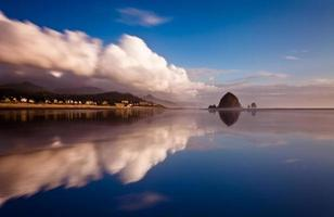mirror reflection of cannon beach with clouds